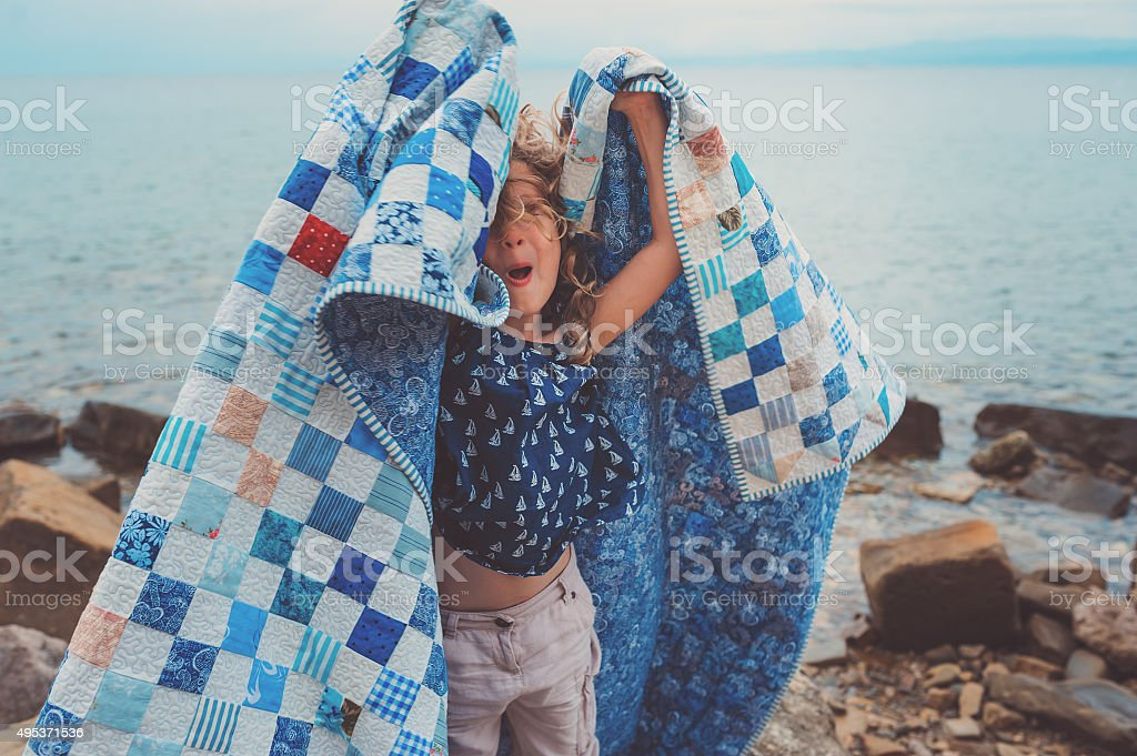 happy child girl covered in blanket at sea, cozy mood stock photo