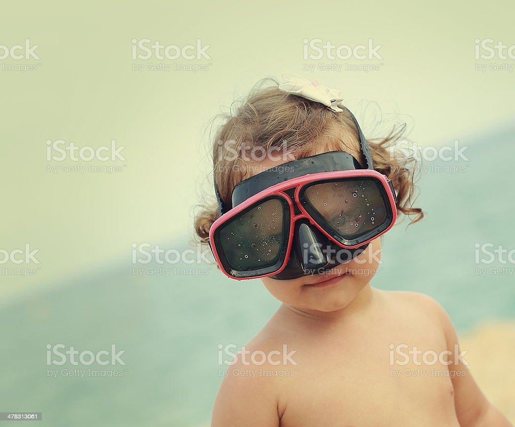 Happy child girl in diving mask smiling on beach royalty-free stock photo