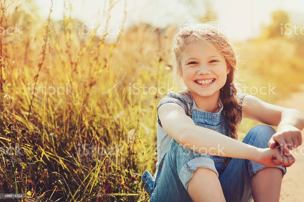 happy child girl in jeans overall playing on sunny field stock photo