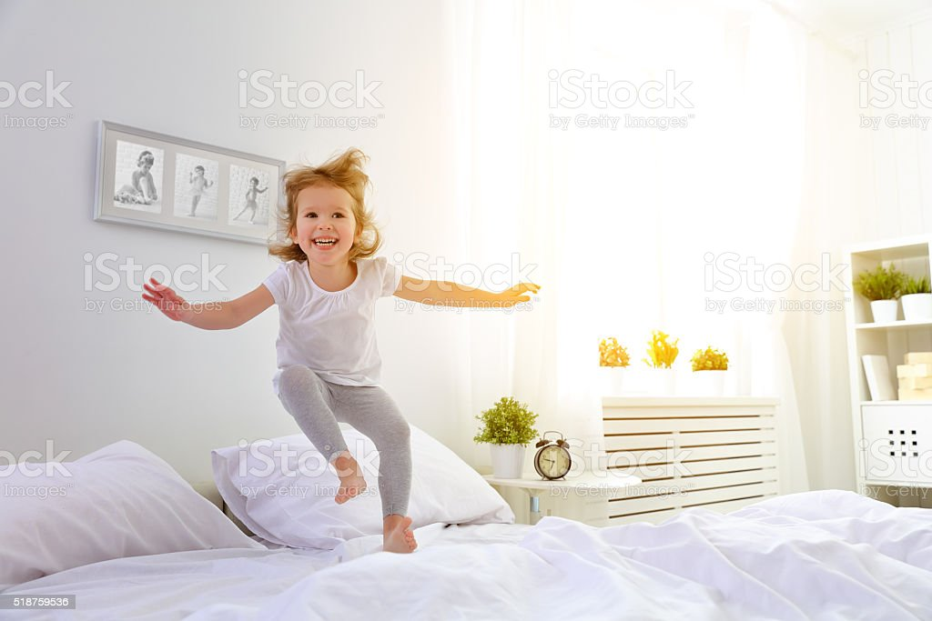 happy child girl jumps and plays bed stock photo