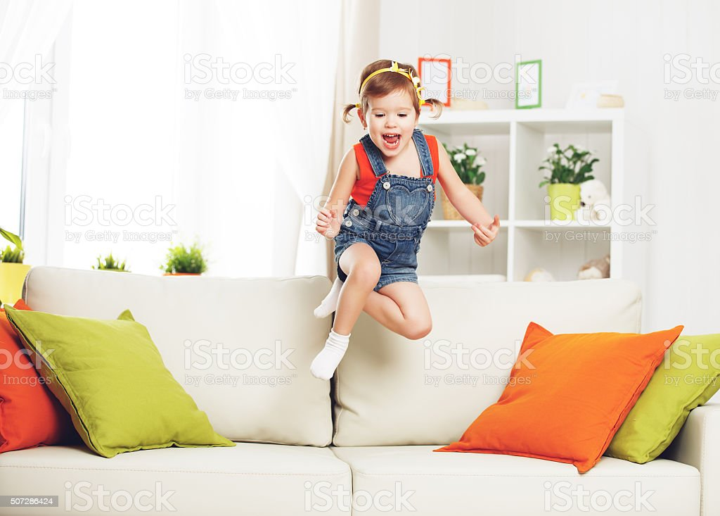 happy child girl playing and jumping on couch at home stock photo