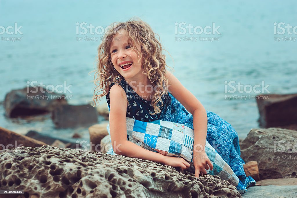 happy child girl relaxing on the beach in cozy blanket stock photo