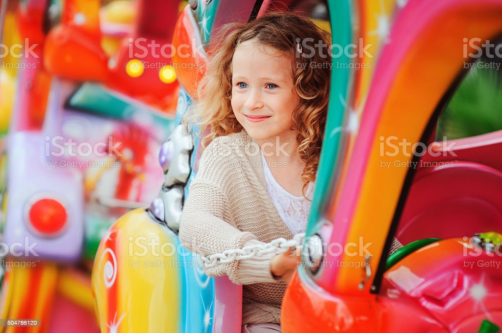 happy child girl riding train on funfair stock photo