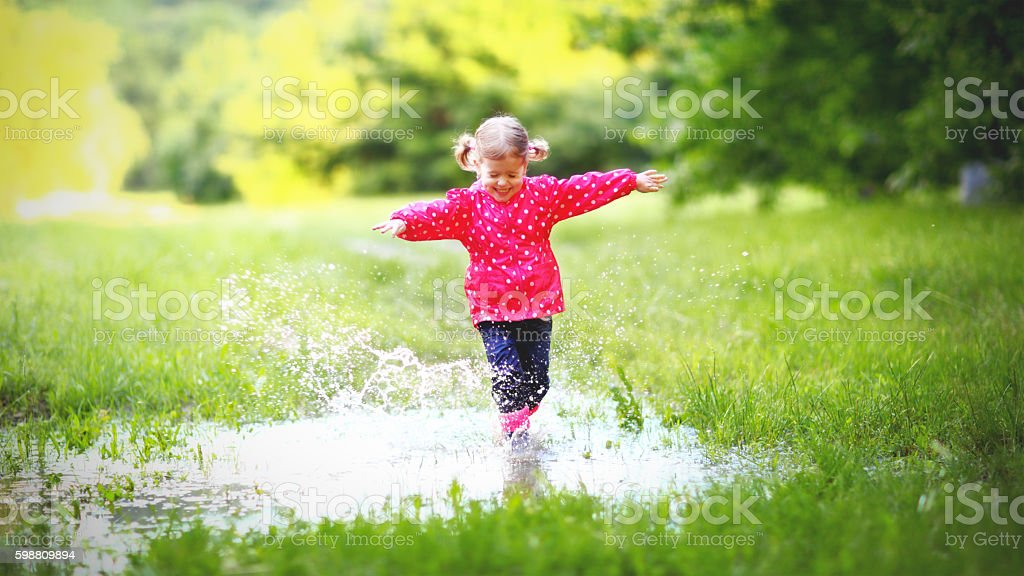 happy child girl running and jumping in puddles after rain stock photo