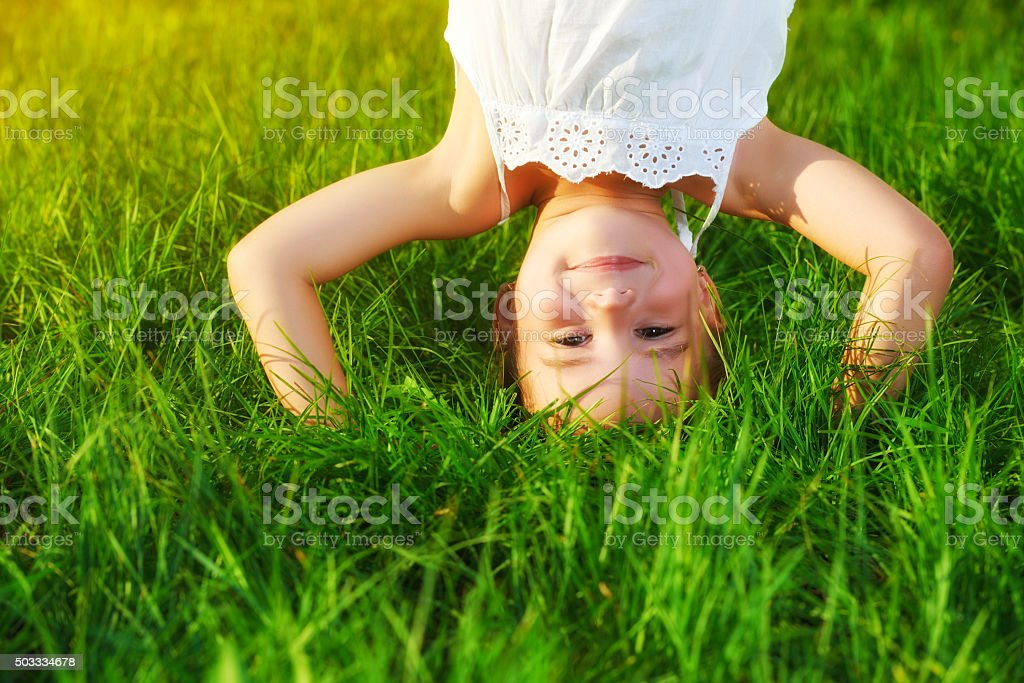 happy child girl standing upside down on head on grass stock photo