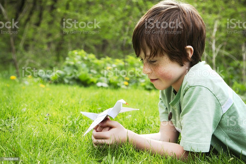 Happy Child Holding a Origami Peace Crane Outside in Nature stock photo