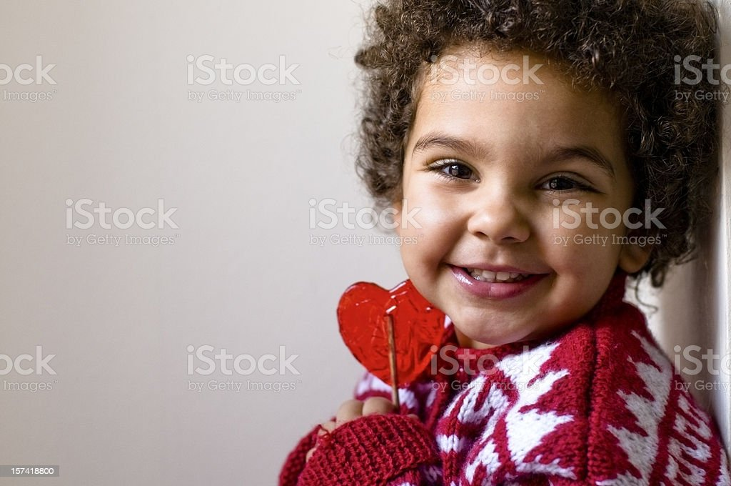 Happy Child Holding Tight Her Heart Shaped Lollipop stock photo