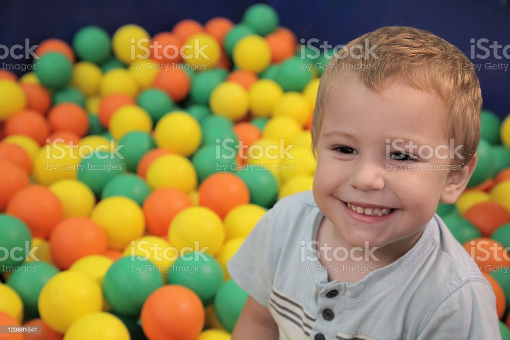 Happy child in multicolored balls royalty-free stock photo