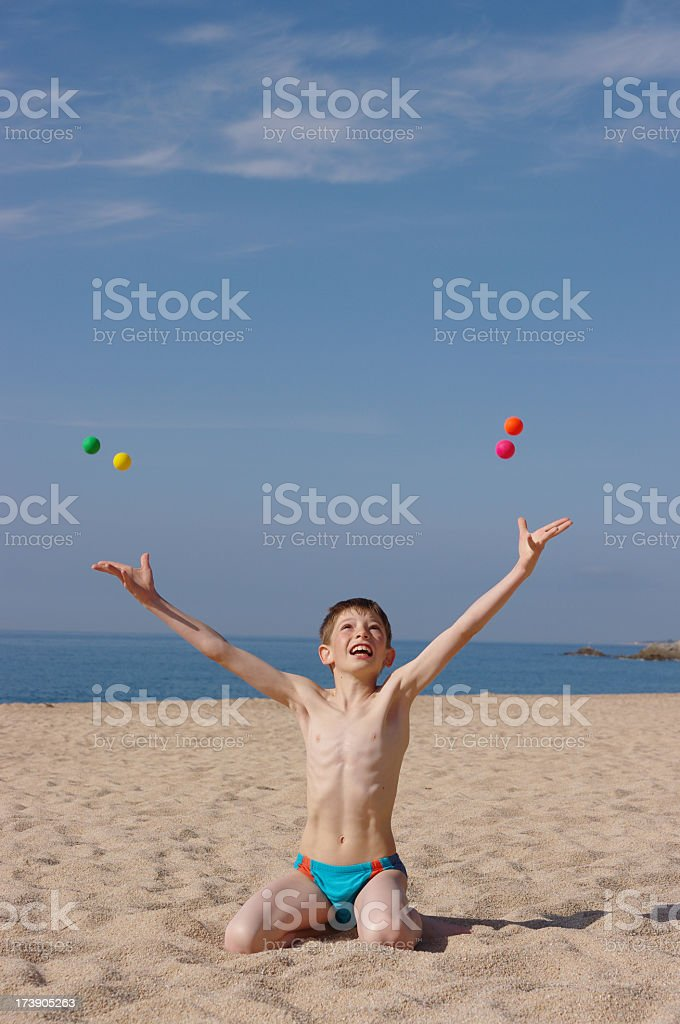 Happy child Juggling with balls on beach royalty-free stock photo