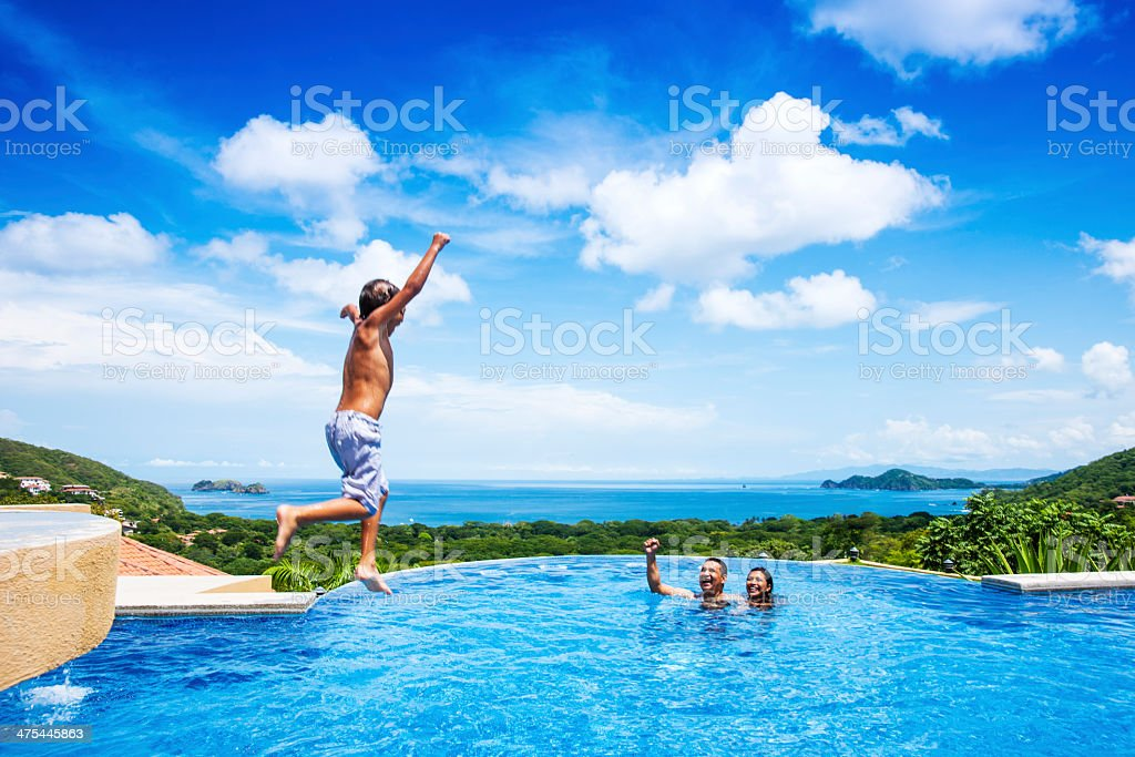 Happy child jumping into a pool in Costa Rica royalty-free stock photo