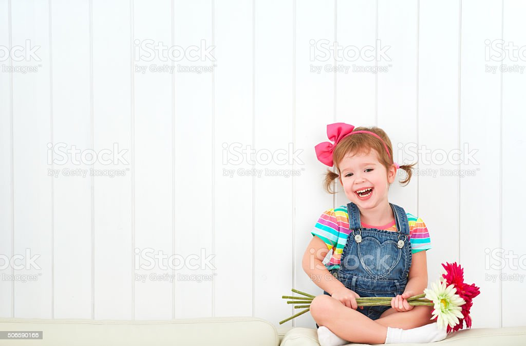 Happy  child little girl with bouquet of gerbera flowers stock photo