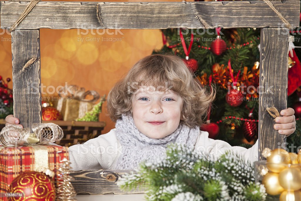 Happy child looking into wooden frame royalty-free stock photo