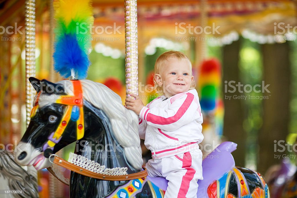 Happy child on a horse fairground ride stock photo