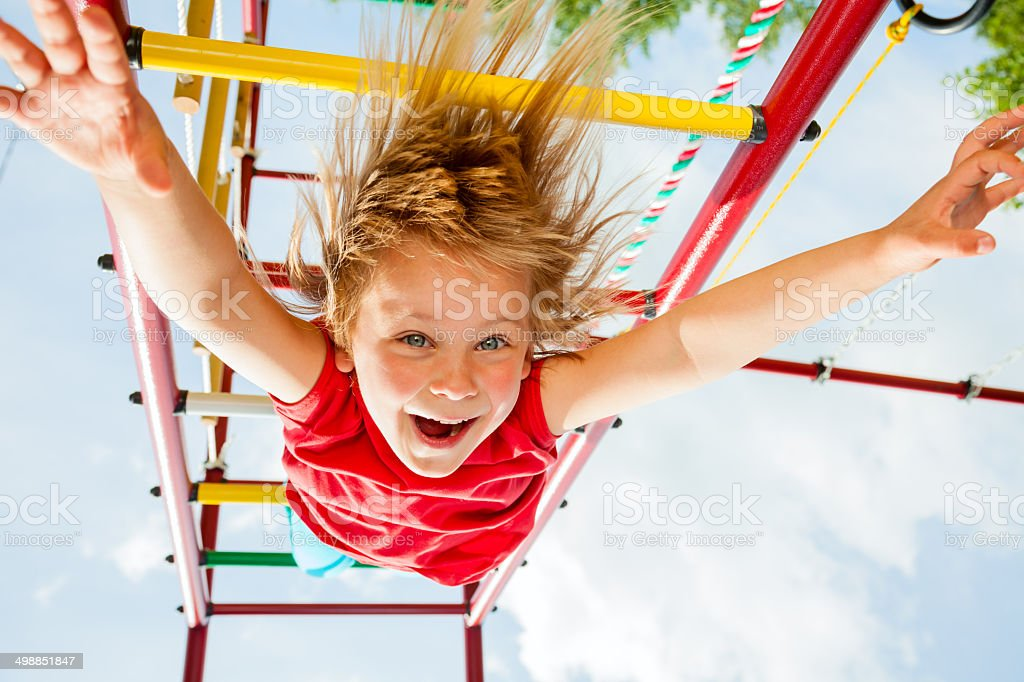 Happy child on a jungle gym stock photo