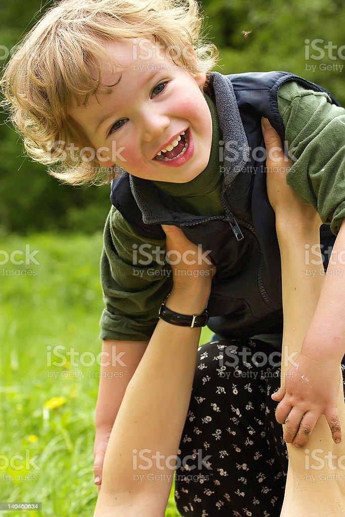 Happy child on hands of careful mum royalty-free stock photo