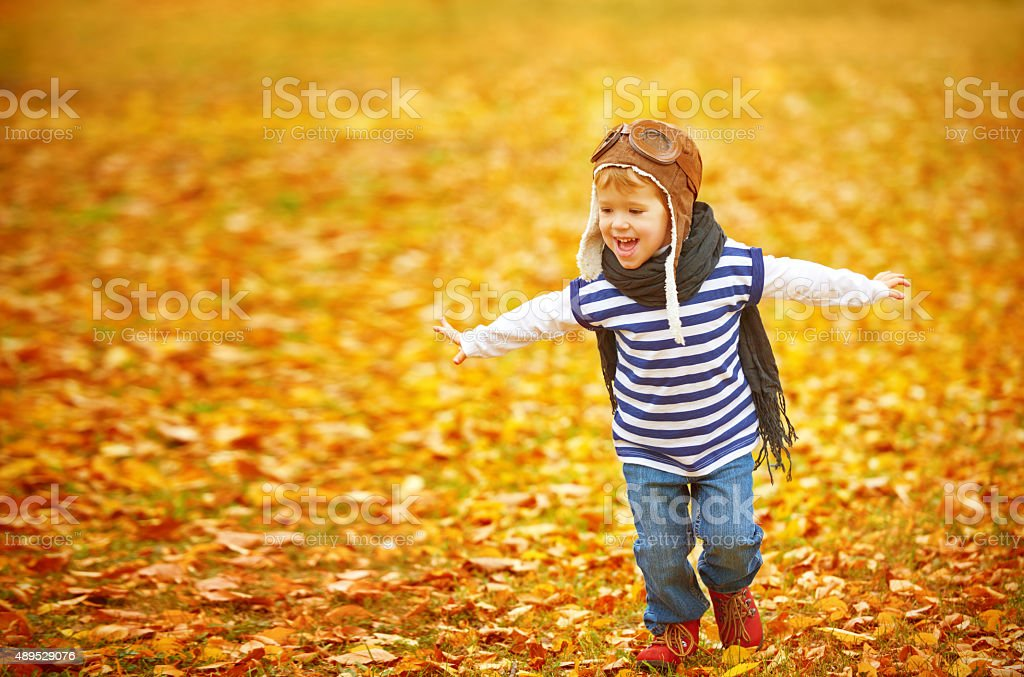 happy child playing pilot aviator outdoors in autumn stock photo