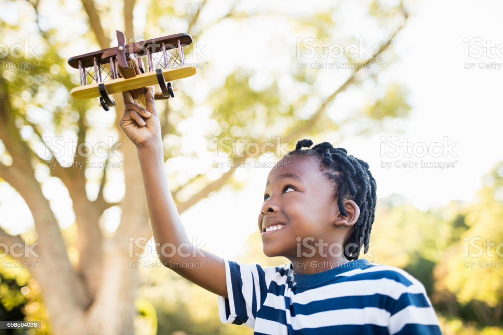 Happy child playing with a plane stock photo