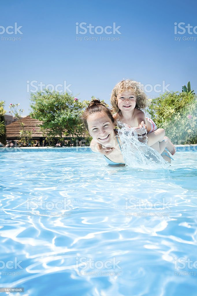 Happy child playing with mother in pool royalty-free stock photo