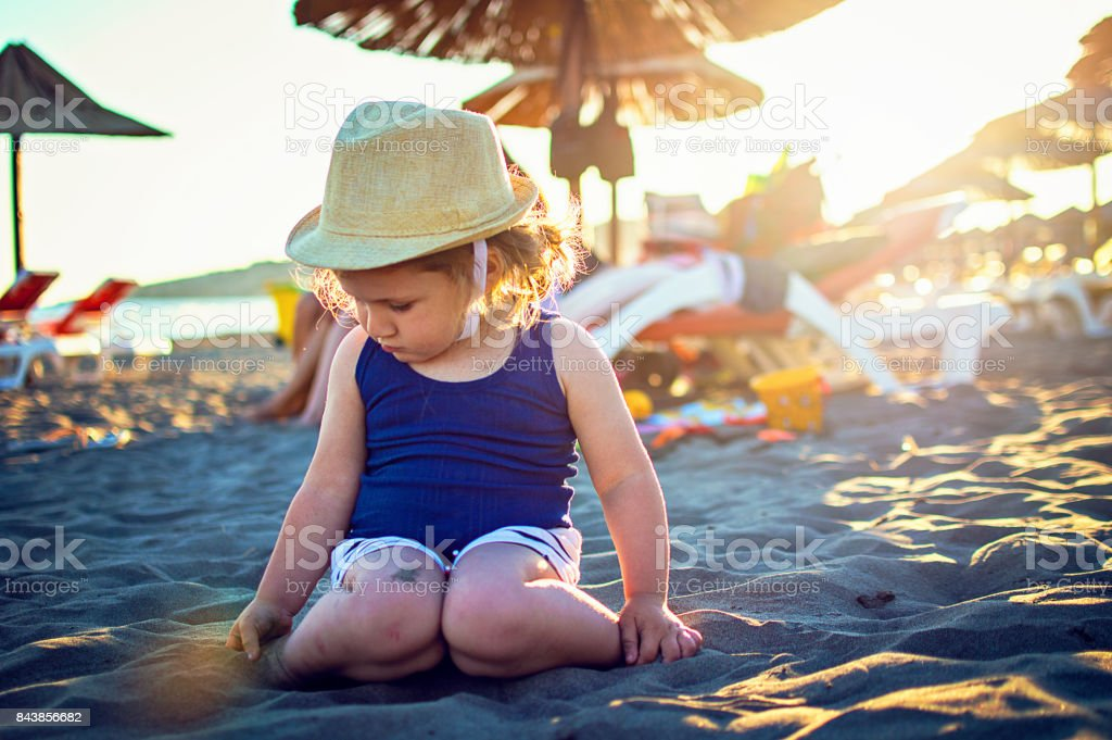 Happy child playing with sand sea beach stock photo
