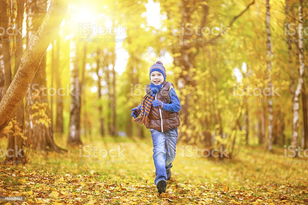 Happy child running in autumn park royalty-free stock photo