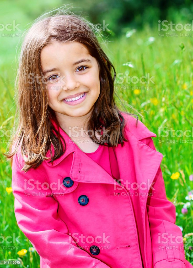 happy child sitting in a grass of a flower garden stock photo