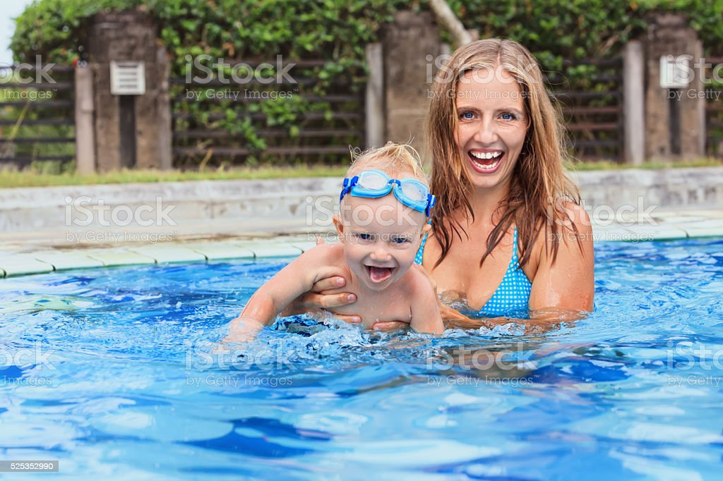 Happy child swim with beautiful mother in pool stock photo