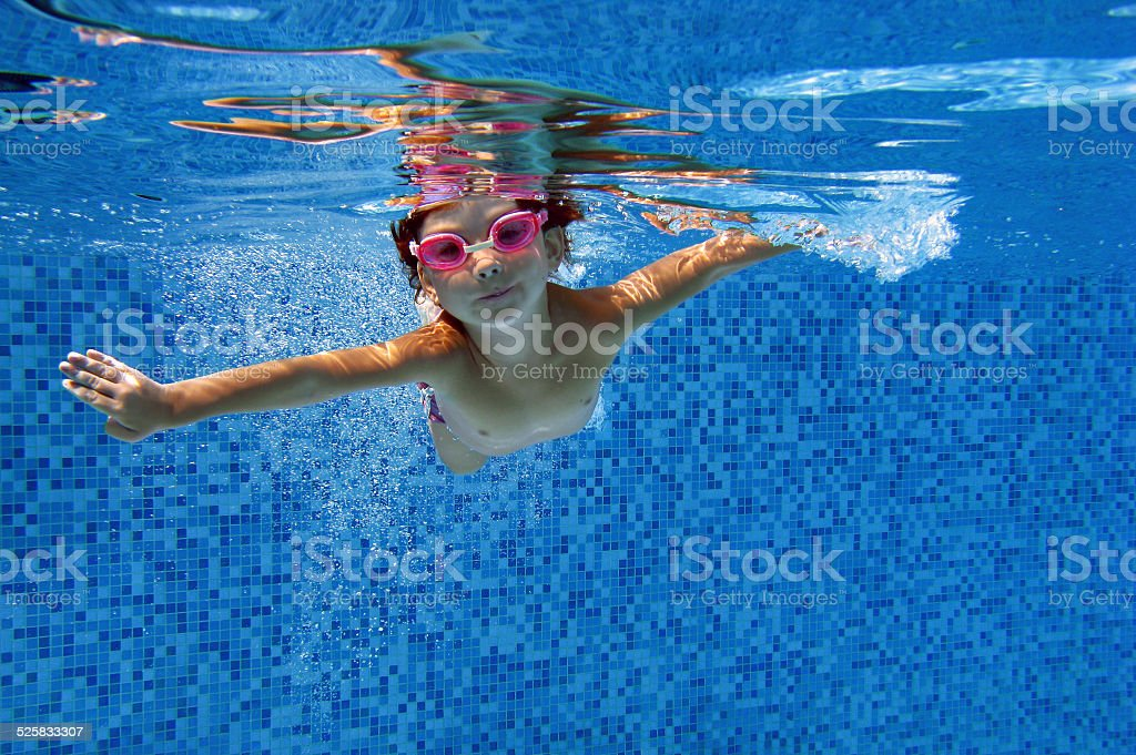 Happy child swims underwater in swimming pool stock photo