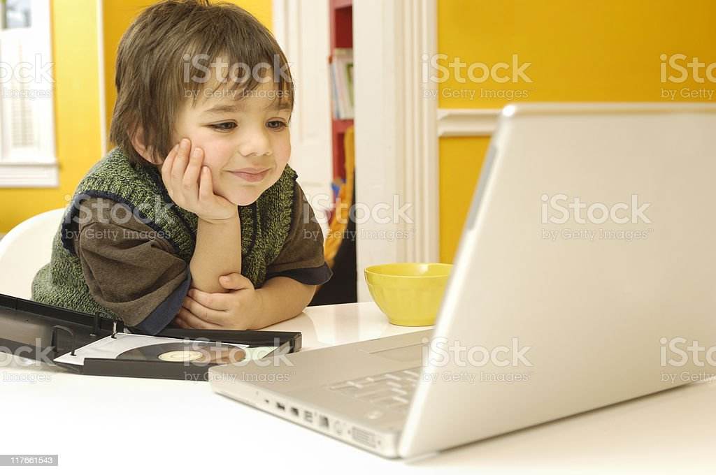 Happy child watching an educational DVD royalty-free stock photo