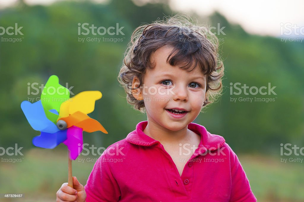 Happy child with colorful windmill stock photo