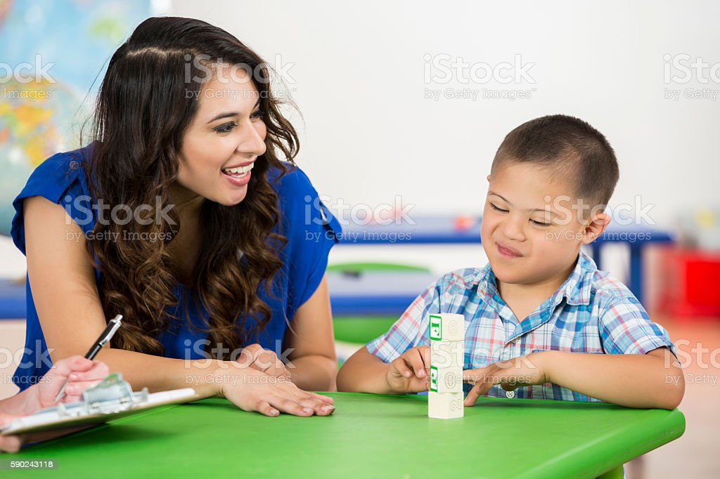 Happy child with Down Syndrome accomplishing task in school stock photo