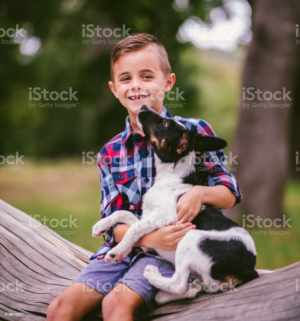 Happy child with his puppy dog on his lap stock photo