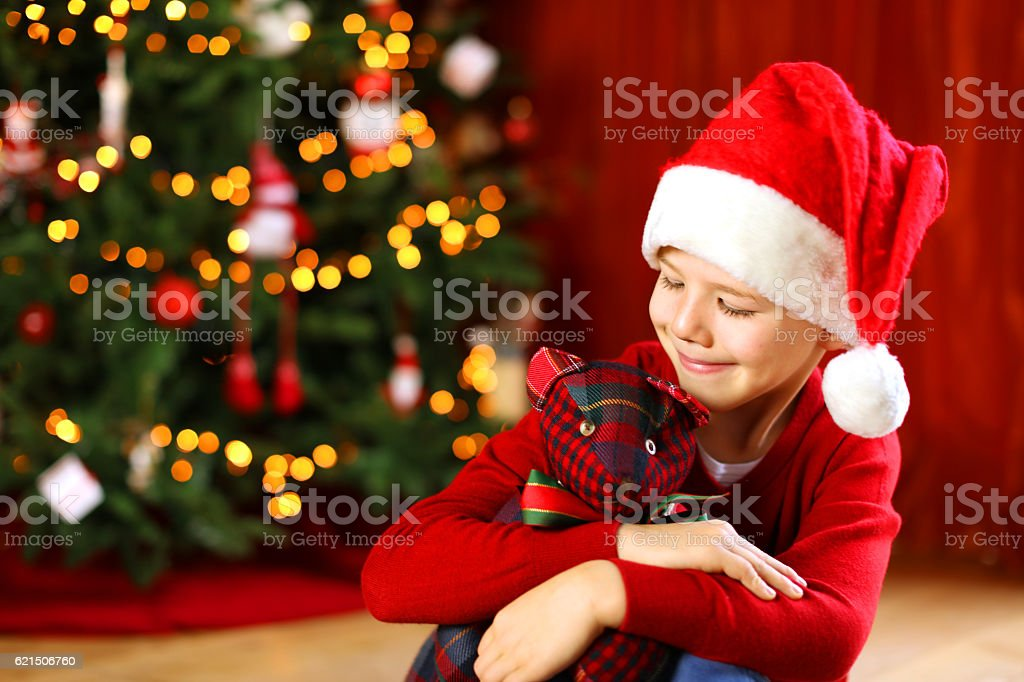 Happy Child with Santa Hat at a Christmas Tree stock photo