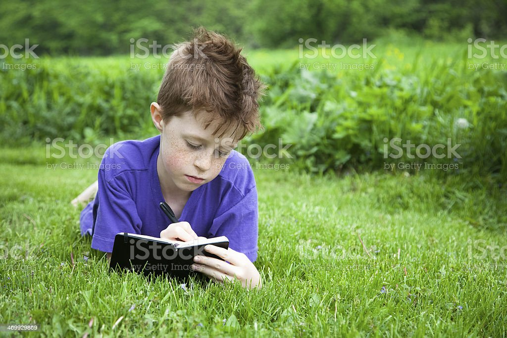 Happy Child Writing in a Journal Outside stock photo