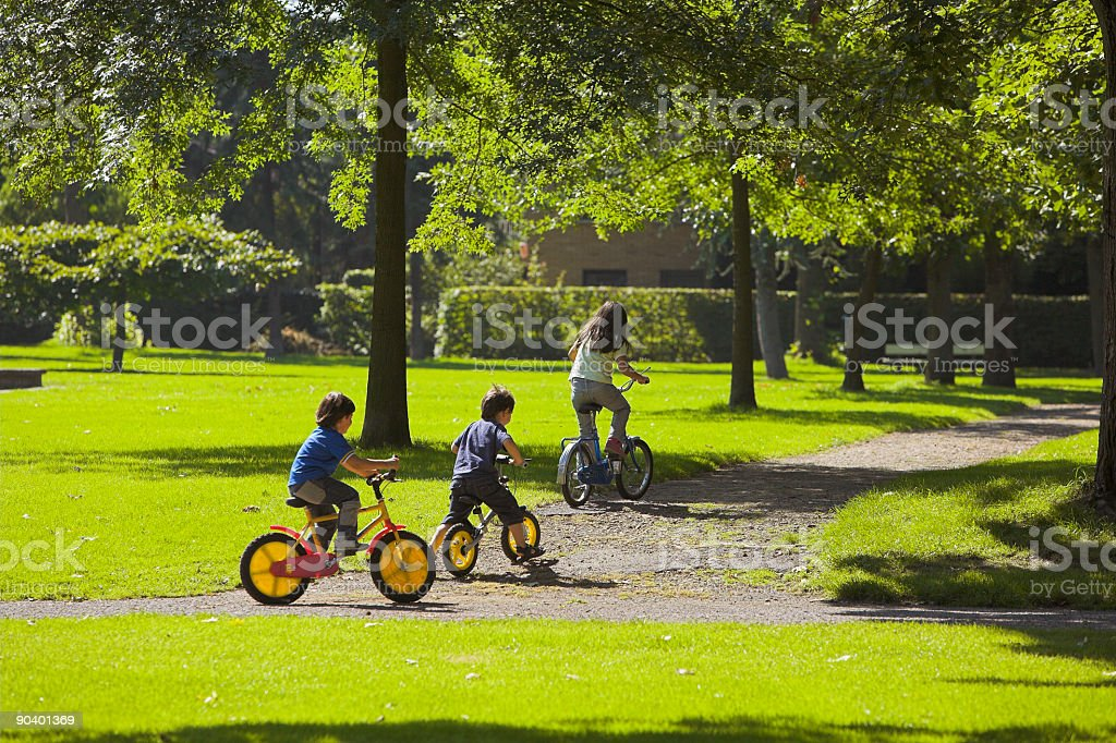 Happy childhood - Three Children cycling in park stock photo