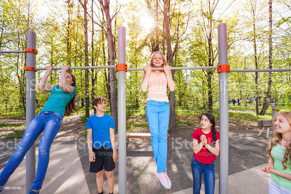 Happy children are chinning up on the playground stock photo