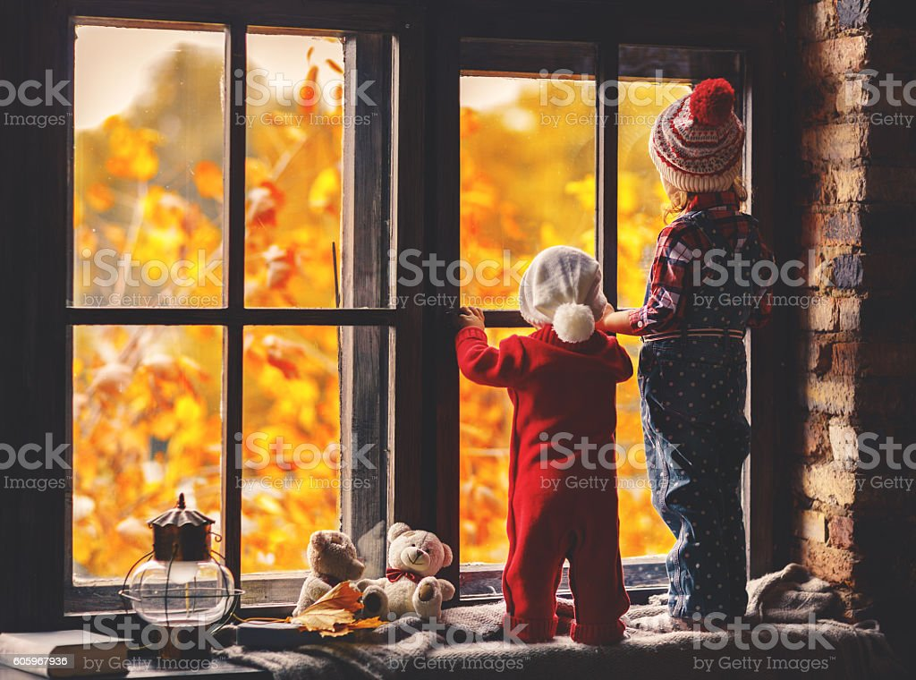 happy children brother and sister looking through windows in fal stock photo