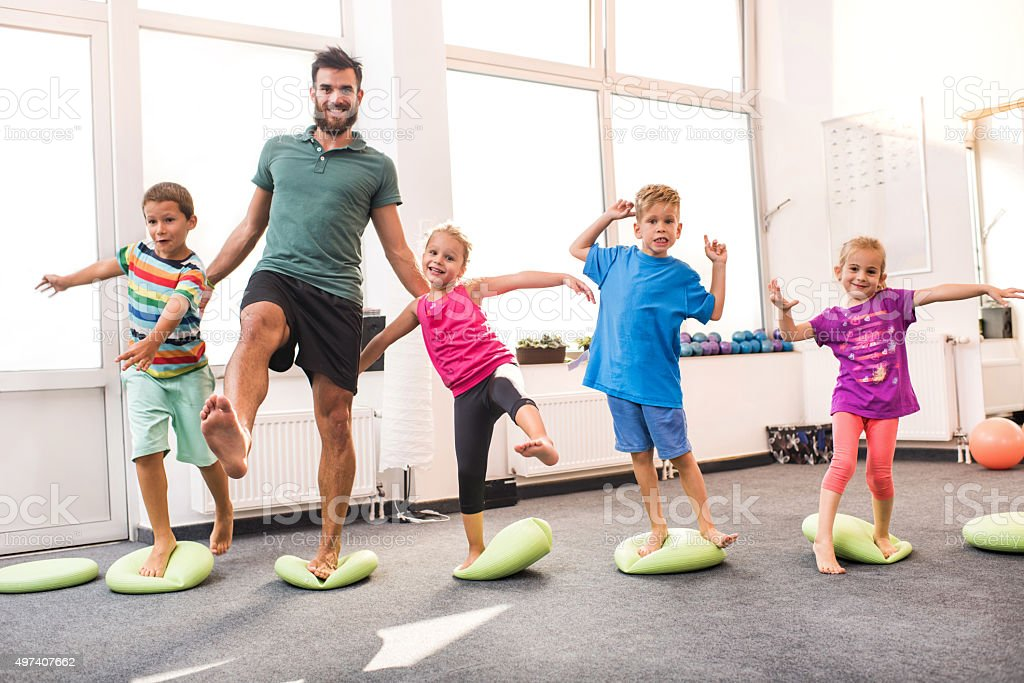 Happy children doing balance exercises with their coach. stock photo