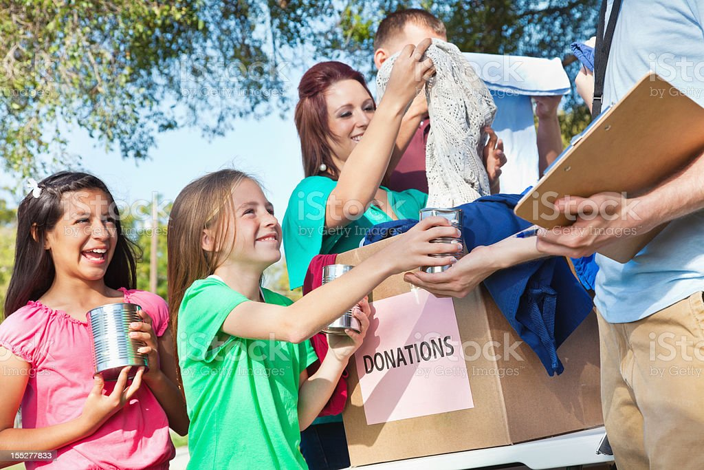 Happy children donating cans and clothes at donation center royalty-free stock photo