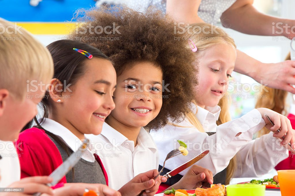 Happy children eating dinner at school stock photo