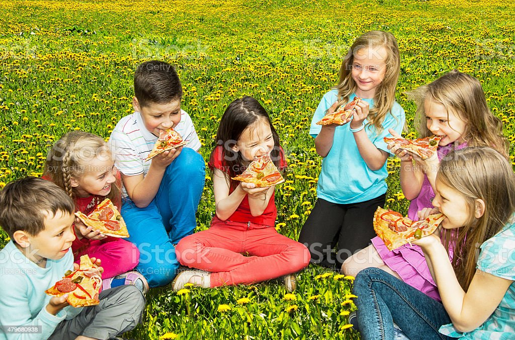 Happy children eating pizza stock photo