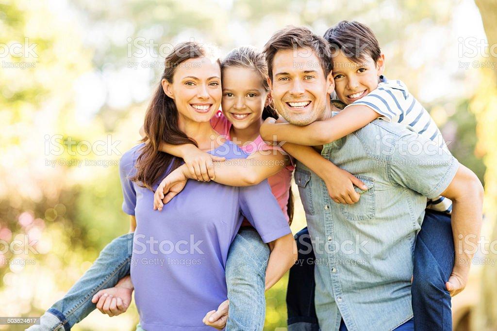 Happy Children Enjoying Piggyback Ride On Parents stock photo