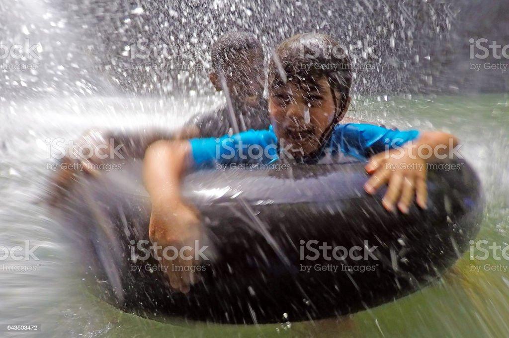 Happy children having fun under a waterfall stock photo