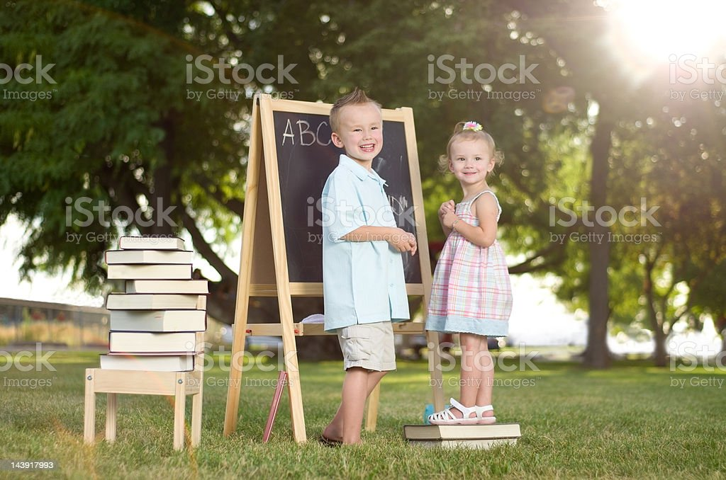 Happy children learning in outdoor setting stock photo