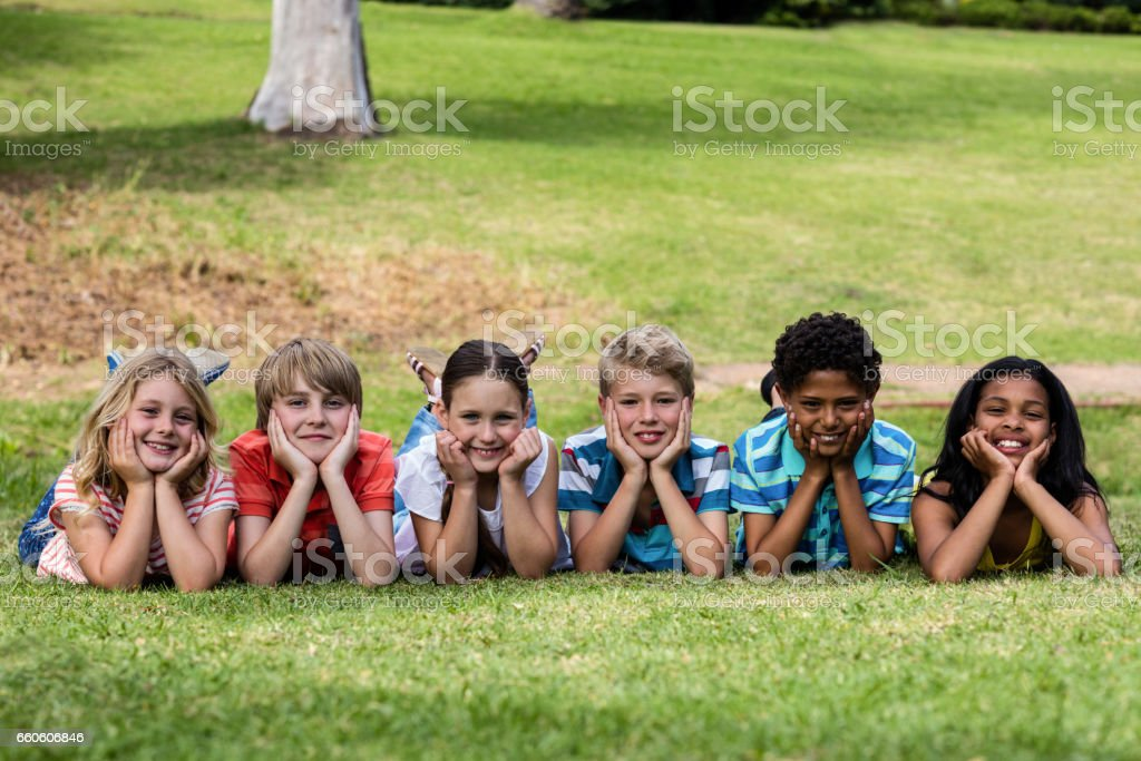 Happy children lying on grass stock photo