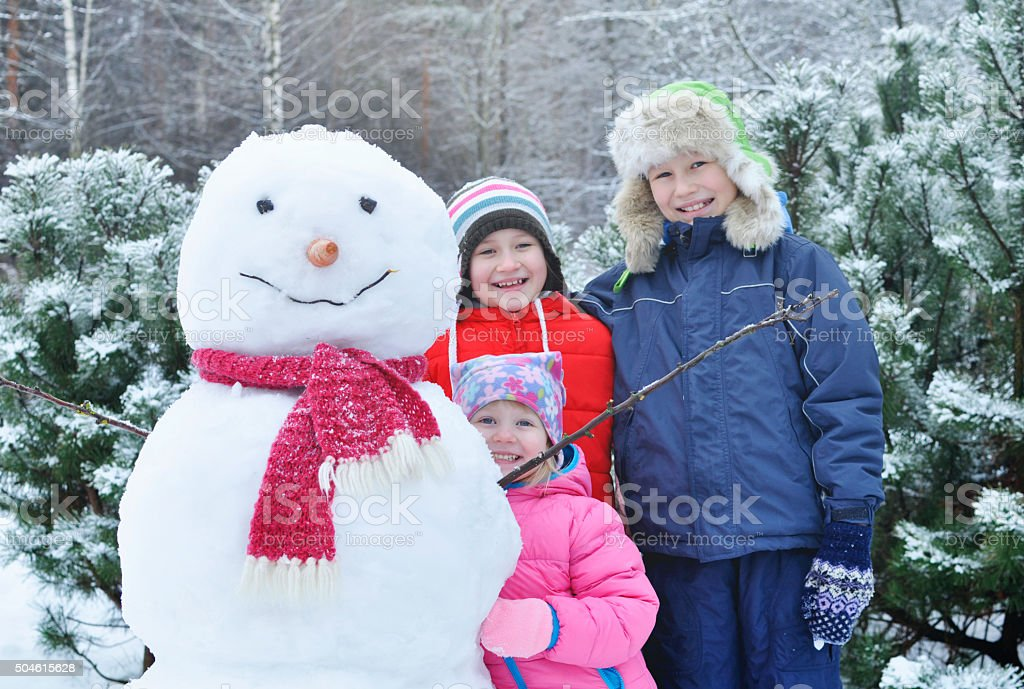 Happy children make a snowman in the winter stock photo