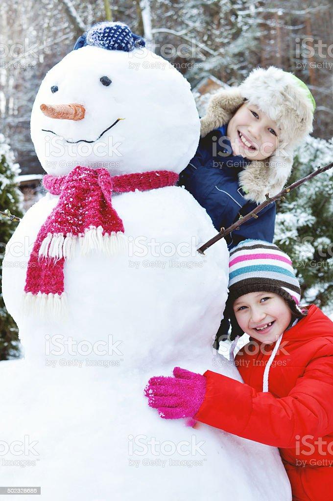 Happy children make a snowman stock photo