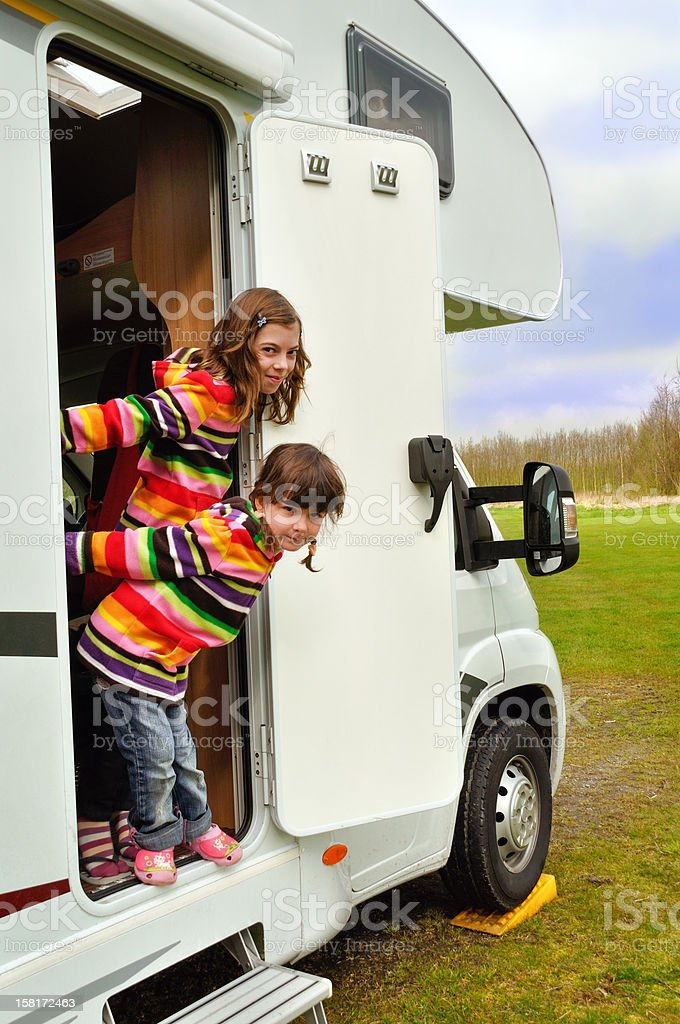 Happy children near camper on family vacation royalty-free stock photo