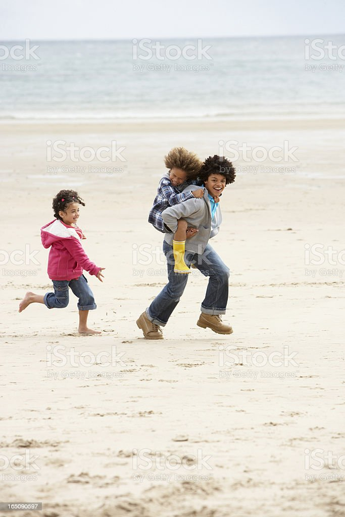 Happy children playing piggyback on beach royalty-free stock photo