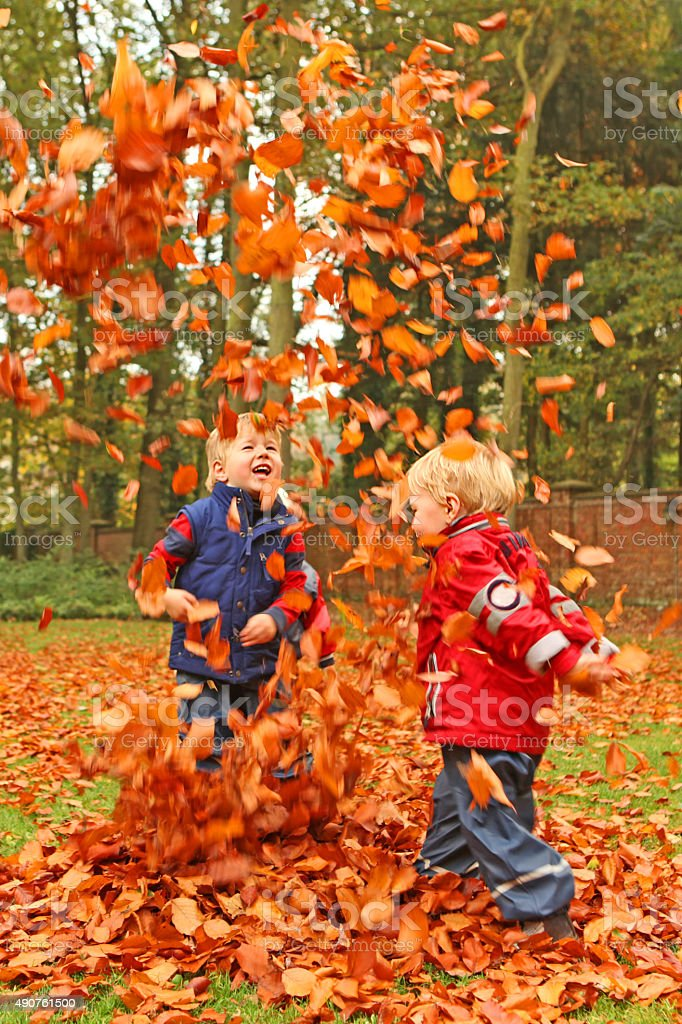 Happy Children Playing with Colorful Autumn Leaves Outdoors stock photo