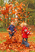Happy Children Playing with Colorful Autumn Leaves Outdoors